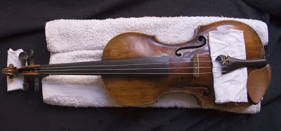 A rolled towel stabilises the postion of the violin.